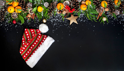 Christmas composition with branch of Christmas tree, tangerines, Christmas ornaments, pine cones on a black background.