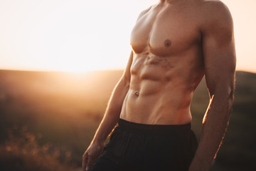Crop muscular man in sunset