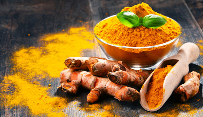Composition with bowl of turmeric powder on wooden table
