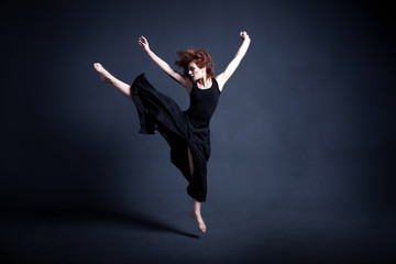 Dancer in a black dress is dancing in the dark studio