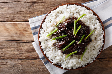 Mongolian beef with sauce and garnish of rice. Horizontal top view