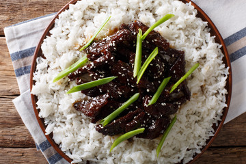 Mongolian food: beef in soy sauce with sesame and green onions closeup. horizontal top view