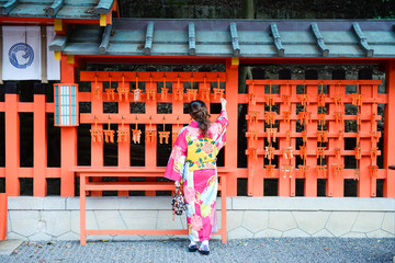 Asian woman was wearing kimono is looking at small torii charm and smiling inside Fujimi Inari temple in Kyoto, Japan.