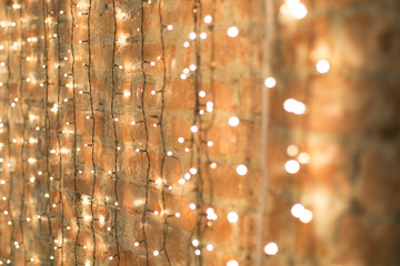 Christmas electric garland on white brick wall background