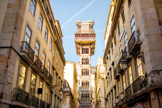 Street view on the old buildings with famous saint Justa metal lift during the sunrise in Lisbon city, Portugal