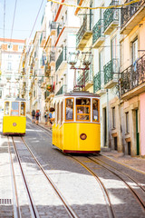 Street view with famous yellow funicular tram in Lisbon during the sunny day in Portugal