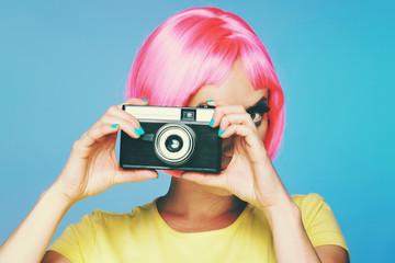 femme à perruque rose photographiant avec appareil photo argentique vintage