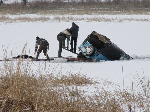 Men try to pull the car drowned under the ice