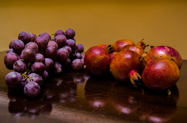 Vintage background of a bunch of purple grapes and pomegranate reflected in a table.