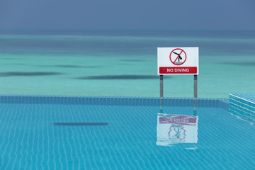 No diving sign at an infinity pool against the beautiful clear blue sea, with space for text