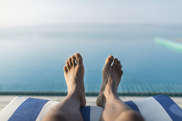 Horizontal orientation of male feet on a sun lounger overlooking an infinity pool towards the ocean, with space for text