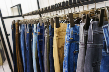 Jeans of different styles on the hanger in the showroom.