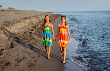 Two little girls walking together on the beach