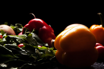 Red and yellow pepper, mushrooms and greenery on dark blue and black backgorund. Artistic vegetable image