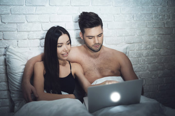 Girl is lying in a dark room in bed with a guy. A guy with a girl in bed is looking at the laptop.