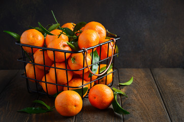 Fresh tangerine clementines with leaves on dark wooden background, selective focus, copy space.