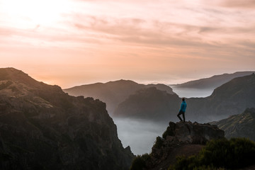 Adult male hiker watching the sunset over the mountain panorama of Madeira, Portugal