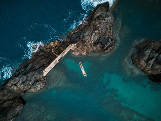 Aerial of an adult male swimming and playing in a natural swimming pool on Madeira, Portugal