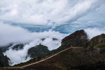 Adult male in yellow jacket gazing over a dramatic cloudscape and mountains on Madeira island, Portugal