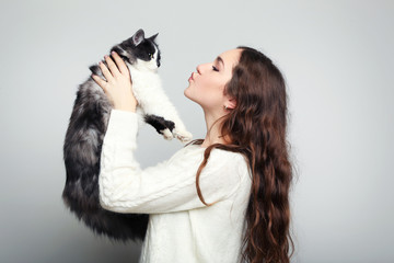 Beautiful young woman holding cat on grey background
