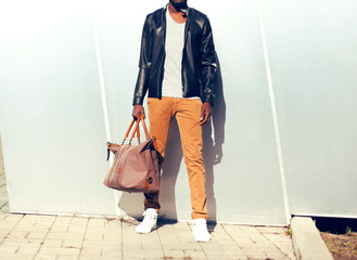 Wall Mural - Fashion man in a black leather jacket with bag in the city