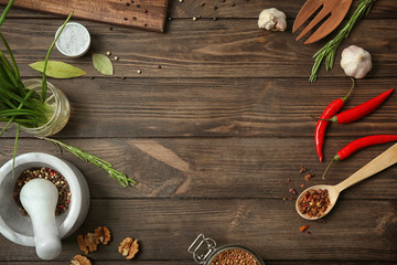 Kitchen utensils, vegetables and spice on wooden background