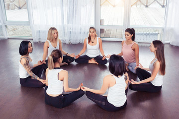 Group of sporty happy people sitting on the gym floor in a circle together, resting and meditating after yoga class, talking about healthy life with instructor indoors. Healthy lifestyle concept