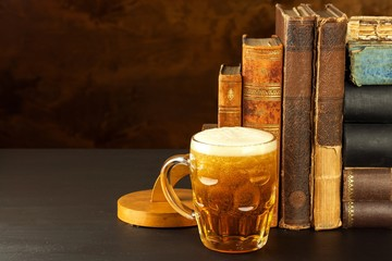 Papiers peints Biere, Cidre Glass of cold beer and old books. Rest with the book.