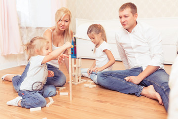 Cheerful family spending time together at home,. Daddy, mommy and little daughters lying on the wooden floor and playing with a wooden tower game.
