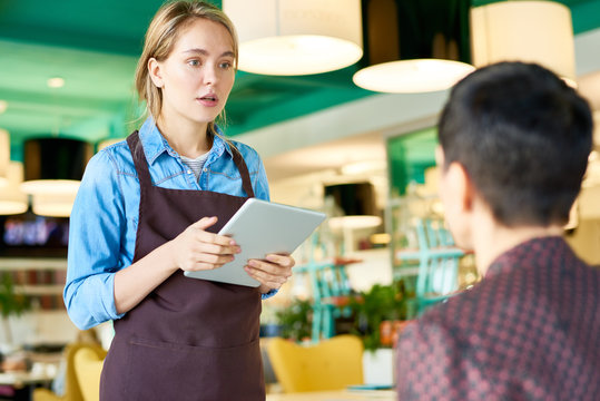 Portrait of young cafe waitress  wearing apron taking order from client using digital tablet, copy space
