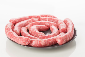 plate of white sausages without cooking