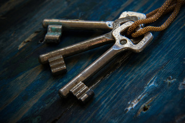 Three antique keys on wooden table