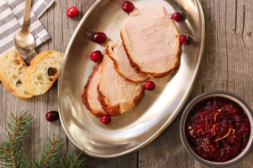 Overhead view of Sliced  roasted Turkey with cranberry sauce on wooden background