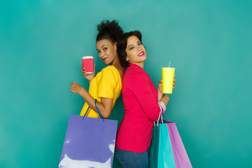 Excited girls with shopping bags and take away drinks