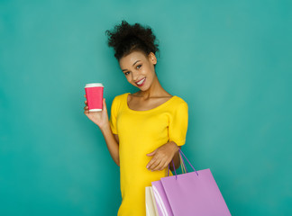 Excited girl with shopping bags and take away drink