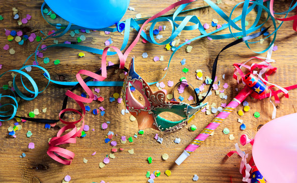 Carnival party. Mask, confetti and serpentines on wooden floor
