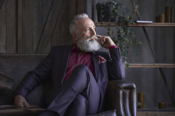 Side view pensive bearded grandfather sitting on sofa in living room. Dreaminess concept