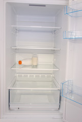 Glass of milk and bottle inside in empty clean refrigerator