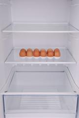 One eggs in open empty refrigerator.