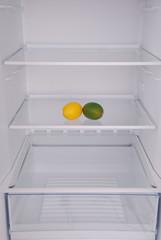 Two lemon in open empty refrigerator.