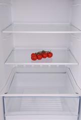 Cherry tomatoes in open empty refrigerator.