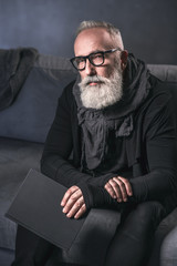 Portrait of serene bearded retire man keeping book in hand while sitting on cozy sofa in apartment. Leisure concept