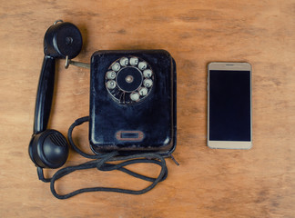 Black vintage phone and a new modern mobile phone on an old wooden background, top view, retro style (old and new concept)
