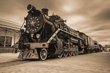 An old black Soviet steam locomotive with a star on the hull. Sepia
