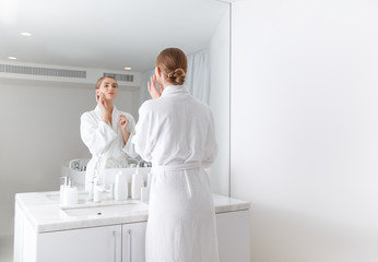 Back view of confident girl applying cream on her cheek while standing in front of the mirror at spa