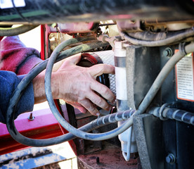 Mechanic installing new air filter in large tractor