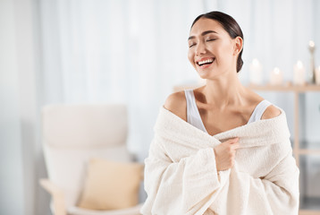 Feeling joy. Waist-up portrait of cheerful young asian woman is sitting on massage couch with closed eyes and expressing gladness while resting in beauty center. She is wearing white bathrobe. Copy