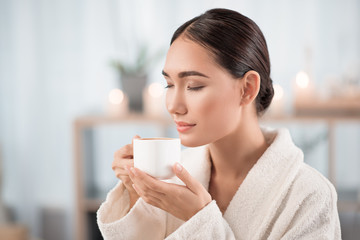 Great aroma. Gorgeous young asian lady is smelling fresh espresso with closed eyes and expressing satisfaction. She is resting in white bathrobe at beauty salon. Candles in background