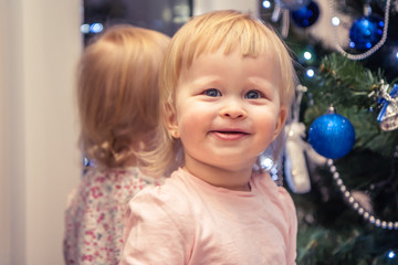 Cute cheerful baby girl waiting for Christmas gift with Christmas tree on background at home