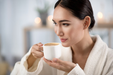 My favorite beverage. Attractive optimistic asian girl is drinking fresh coffee while relaxing in wellness center. She is looking aside with smile. Shelves with candles in background